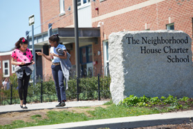 two girls walking past the NHCS stone sign outside the school